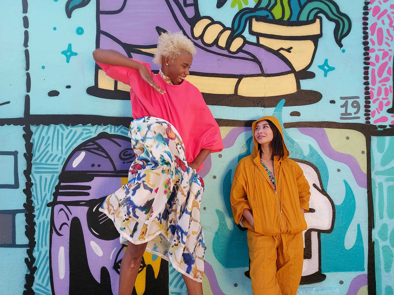 Photo captured by Galaxy A80's Wide-angle lens of two women, one tall and one short, in front of a graffiti wall.